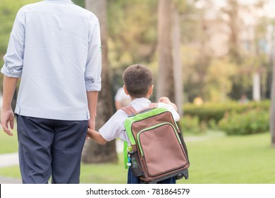 Father and son hold hands together are walking in the garden at evening