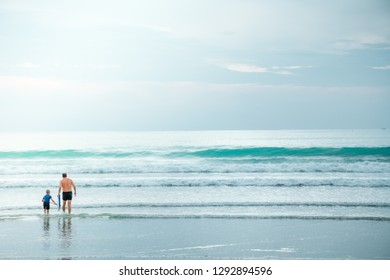 Father and son holding boogie board or bodyboard walking into the shallow water sea with sunlight and sky on vacation. Dad teaches his son to surfing. Relationship of dad and son. Subject soft focus.