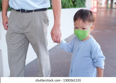 Father and son holding hand, Cute little Asian 2 - 3 years year toddler baby boy child wearing protective medical mask, Dad and son standing in public place (airport / hospital / department store)