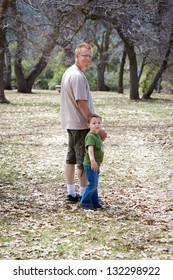 Father and son holding hands and walking in a wooded setting
