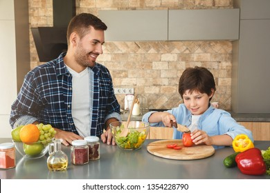 Father and son at home standing in kitchen together man smiling cheerful looking at son cutting vegetables for salad concentrated