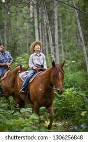Father and son horseriding through forest