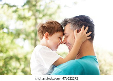 Father and son hugging outdoors, shallow depth of field