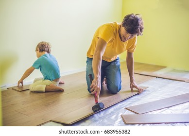 Father and son installing new wooden laminate flooring on a warm film floor. infrared floor heating system under laminate floor
