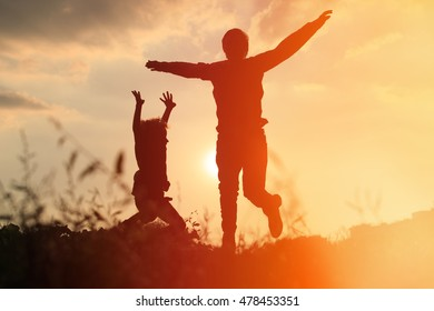 father and son jumping at sunset sky