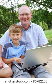father and son with laptop outdoors