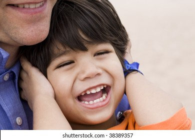 Father and son laughing together on beach