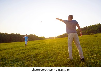Father and son launch paper airplanes. Warm summer evening.