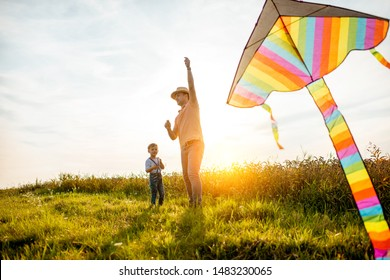 Father with son launching colorful air kite on the field during the sunset. Concept of a happy family having fun during the summer activity