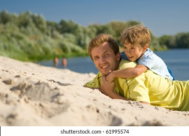 The father and the son lie on sandy to river bank and smile