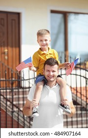 Father and son with little American flags beside their house