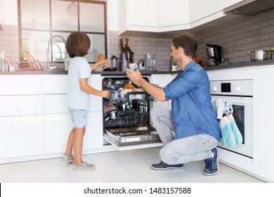 Father and son loading dishwasher together