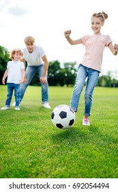 father with son looking at cute little girl kicking soccer ball on meadow
