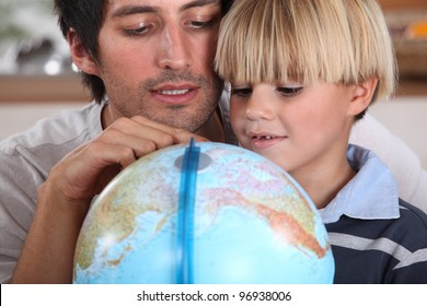Father and son looking at globe