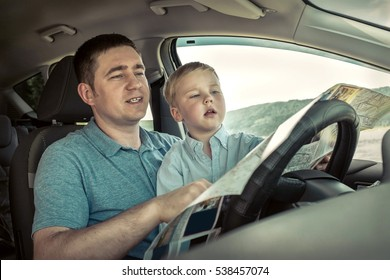 Father and son looking on map in car