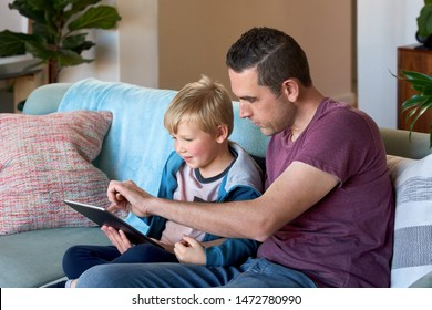 Father and son looking at tablet device screen together, playing game puzzle at home