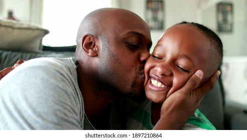 Father and son love and affection. Parent kissing and hugging little boy child. Mixed race African ethnicity