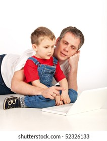 Father and son lying on the floor with laptop on white background