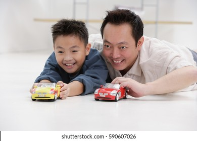 Father and son lying on floor, playing with toy cars