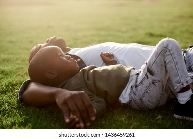 Father and son lying on green grass looking up at sky dreaming aspirational, with sun flare