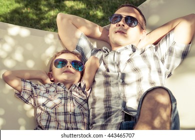 Father and son lying on hammock in the garden at the day time. People having fun on the nature. Concept of friendly family and of summer vacation.