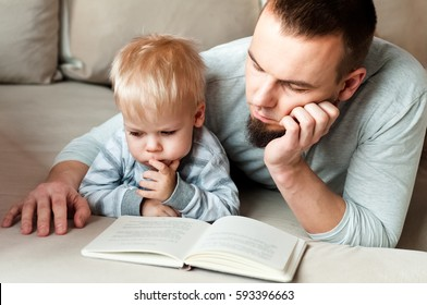 Father and son lying at sofa, they are reading a book.