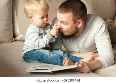 Father and son lying at sofa, they are reading a book. Son is trying to play on father's nose. They have a lot of fun.