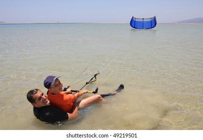 Father and son make water start. Kitesurfing.