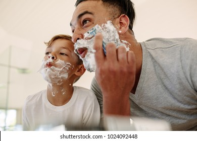 Father and son  making funny faces while shaving in bathroom. Young man and little boy with shaving foam on their faces are shaving and looking into the mirror.