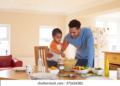 Father And Son Making Pasta Salad In Kitchen