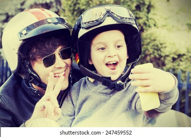 father and son motorcyclists take a selfie on the road