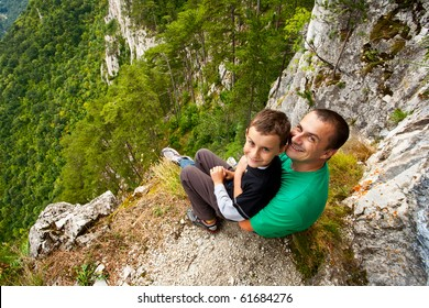 Father and son in mountains, sitting on the edge of a cliff
