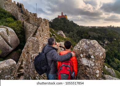 father and son observing historical Pena palace from the grounds of a Moorish castle