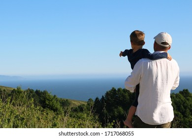 Father and son are on the beach and looking forward. Father and child are together on the sunset on the ocean.
