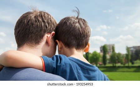 Father and son on a city background. View from the back
