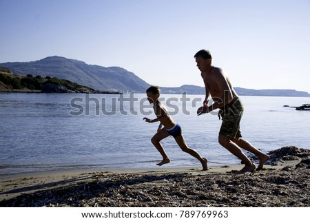 Father and son on the coast are engaged in sports. The father and his son are running along the beach. A young man with his son is running at the beach.