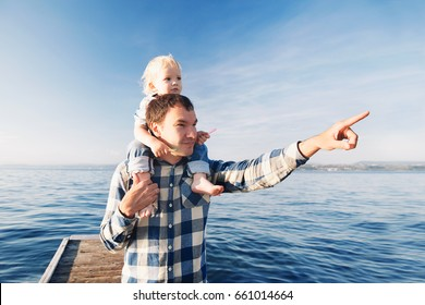 Father and son on sea and sky backgrounds. Little boy is sitting on father's shoulders and points forward. Parent and child together at summer. Family, Lifestyle, Holidays and Travel concept.