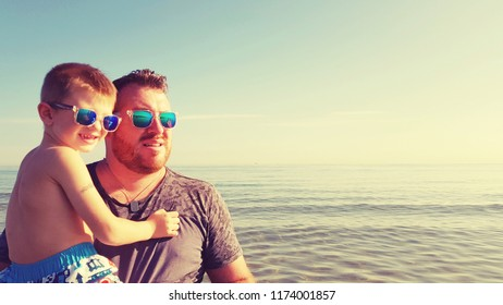 father and son on the sea with sunglasses