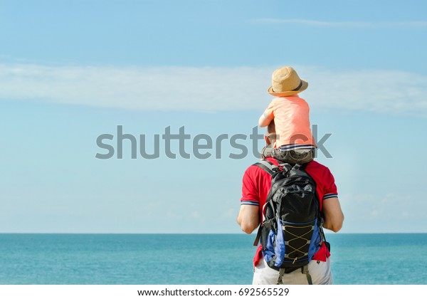 Father and son on their shoulders stand on the sea shore, rear view