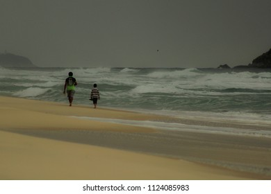 Father and son on a walk along the beach in a cloudy and rainy afternoon at Barra da Tijuca, Rio de Janeiro - Brazil. The darkness of the sky sets a melancholic tone as the ocean waves come and go.