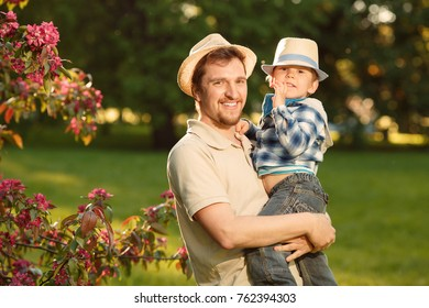 Father and son on a walk in the park. Dad and child play outdoors. Father's Day.