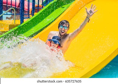 Father and son on a water slide in the water park.