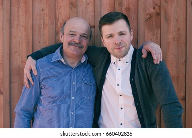 Father and son on wooden background. They look at camera and smile happy.