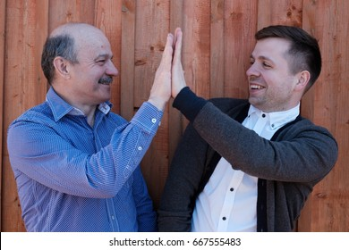 Father and son on wooden background. They celebrate success and clap hands