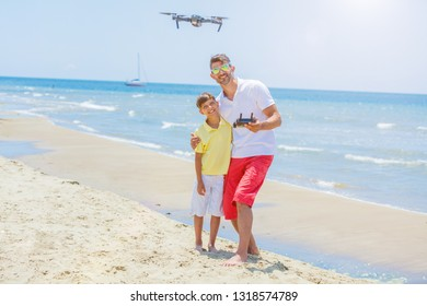 Father and son operating the drone by remote control at the beach. Young man with little boy flying drone at the sea shore, enjoying summer vacation.