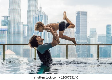 Father and son in outdoor swimming pool with city view in blue sky.