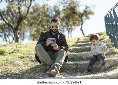 Father and son in outdoors image. Father looking phone while kid playing