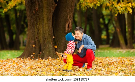 Father and son outdoors, kissing, dressed in colorful clothes. Autumn.