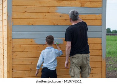 father and son paint a wooden shed with gray paint on the plot