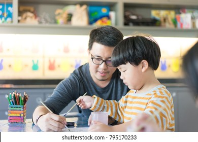 Father and son are painting together in the study room.